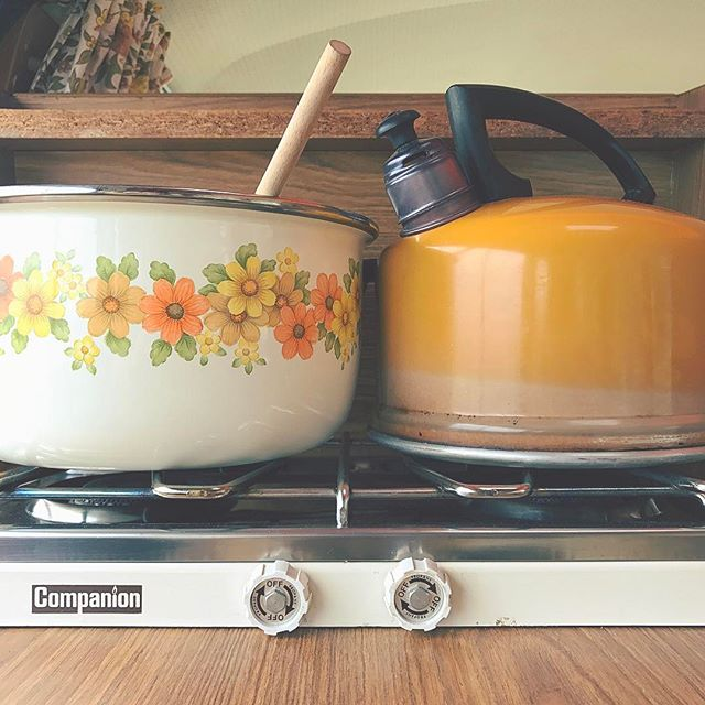 floral metal pot with a wooden spoon in it and an orange metal stove top kettle on top of a portable stove top