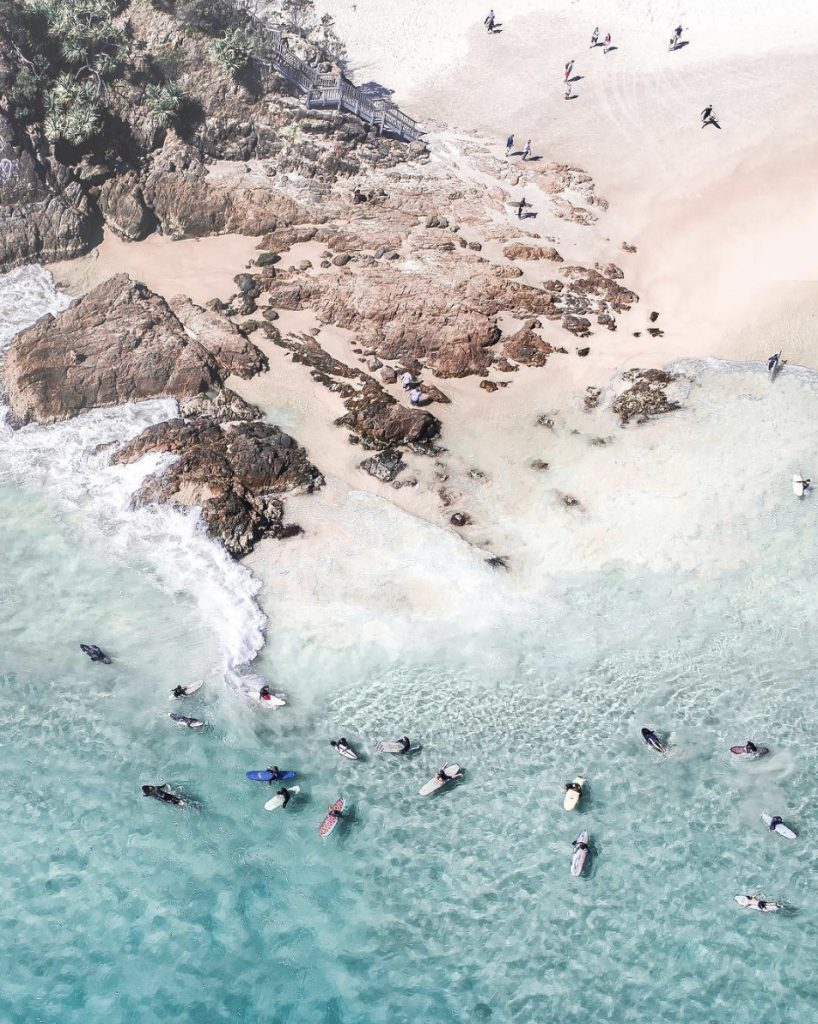 aerial photo of a group of surfers in the ocean at the pass beach