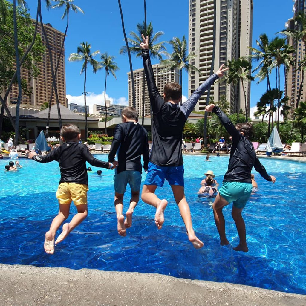 4 boys jumping into a pool