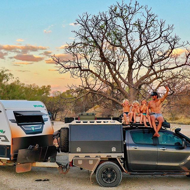 family sitting on top of ute with caravan attached