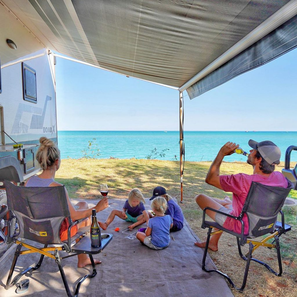 Family lounging outside camper van over looking the ocean