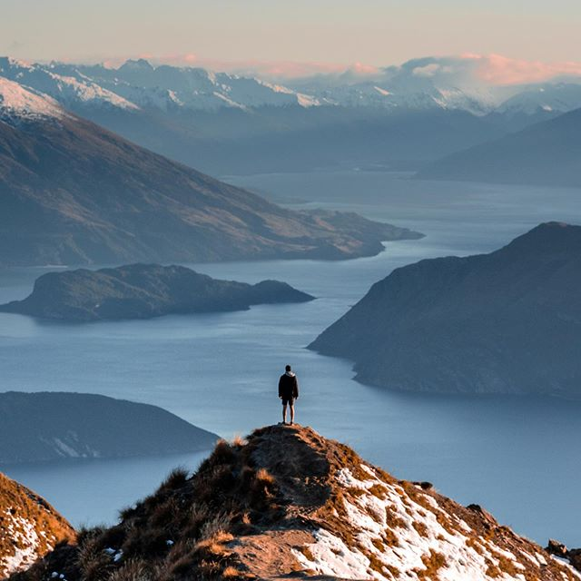 man standing with a mountain view of lake wanaka